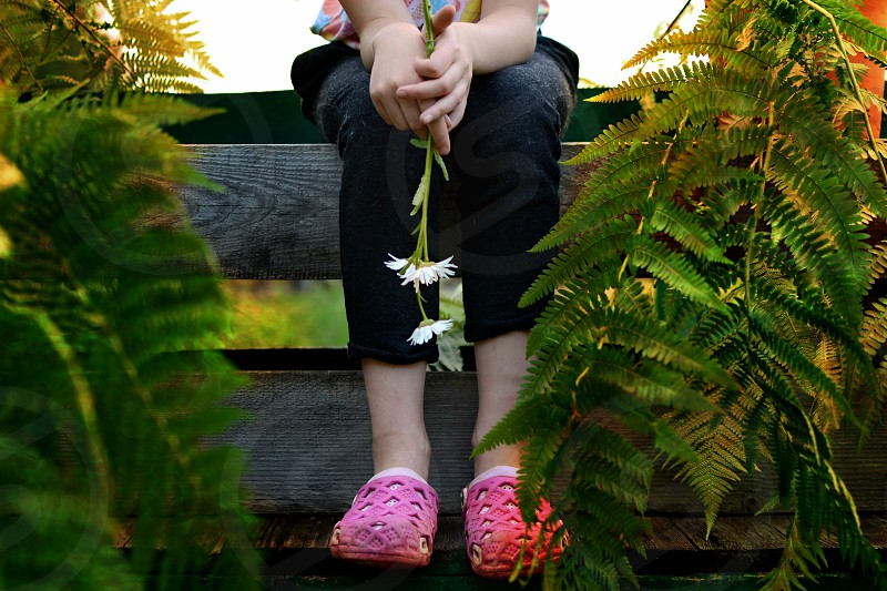 Girl sitting on a bench surrounded by potted plants photo