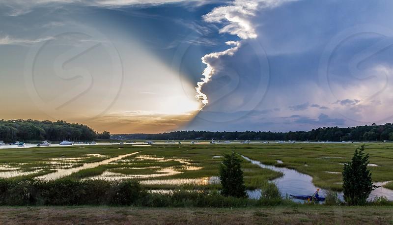 Kayaking at sunset. Clouds sky sunset kayak marsh coast ocean boats. photo