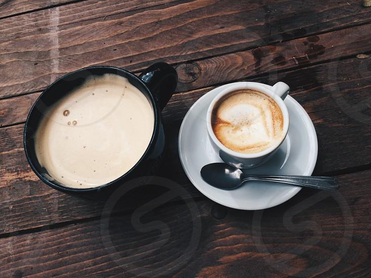 black ceramic teacup brown coffee beside white ceramic teacup on white saucer photo