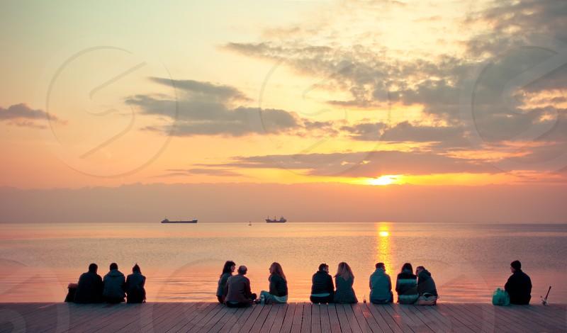 People At The Dock Enjoying The Sunset photo