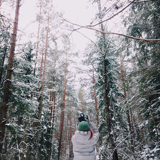 person in white hoodie taking photo of green trees covered with white snow during daytime photo