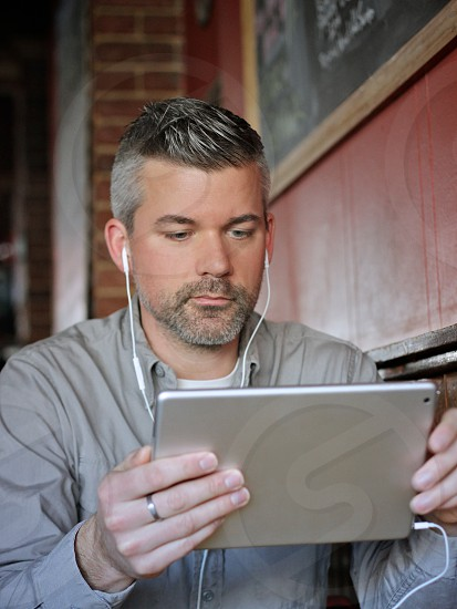 man in a grey button down shirt looking at an ipad photo