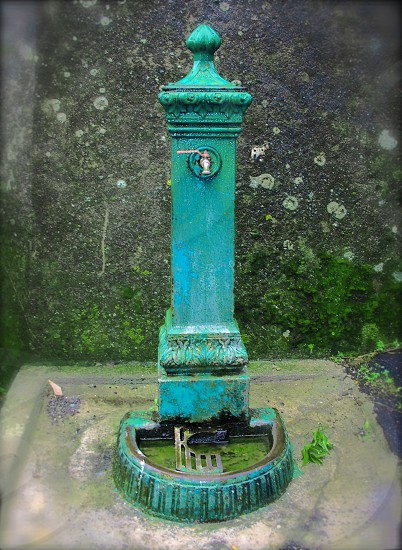 Antique blue stone water spout pole photo
