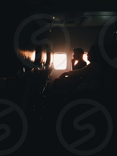 man and woman seated inside airplane photo