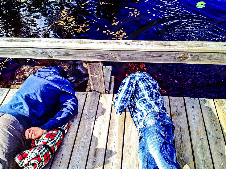 Bridge pier bay water kids boys Explore lying looking lake sea hay straw friends Summer summervacation wooden pier Wood trees spring playing Fun having Fun fishing Reflection  photo