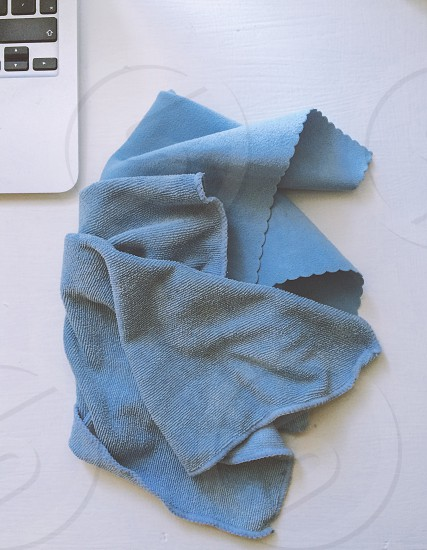 gray cleaning towel beside silver and black laptop computer photo