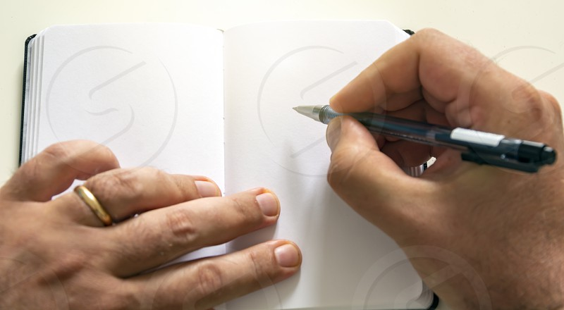 male hands holding a ballpoint pen to write on the blank pages of an open notebook. Creative moment. Inspiration. photo
