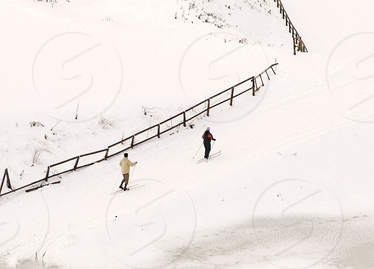 two people skiing on a snow-covered field with a wooden fence photo