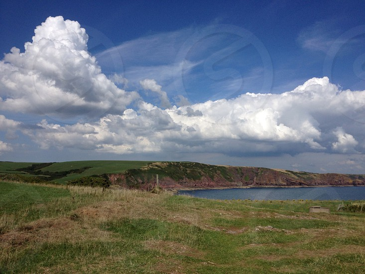 lake surrounded by green grass hills and large white clouds in the blue sky photo