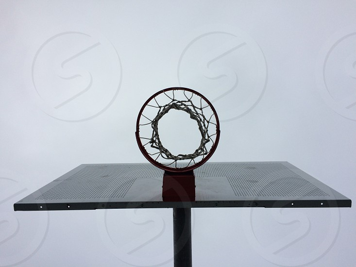 A view from below a basketball hoop and backboard with a grey overcast sky photo