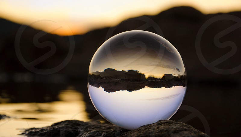 Clear crystal ball seating on rock photo