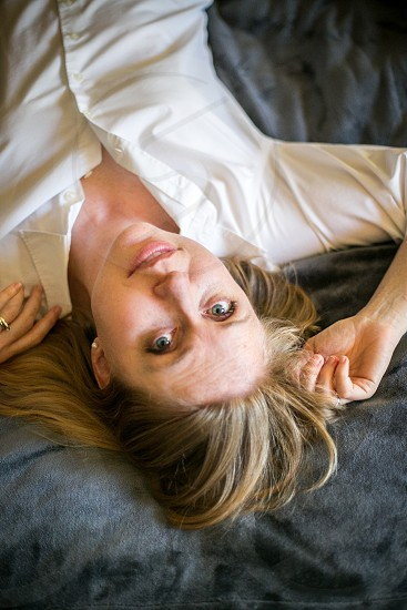 A young woman laying on her back in the floor upside down with a slight smile while looking at the camera. Blouse hair pearl earrings Caucasian girl lady relaxed comfortable natural honest home blue carpet white. photo