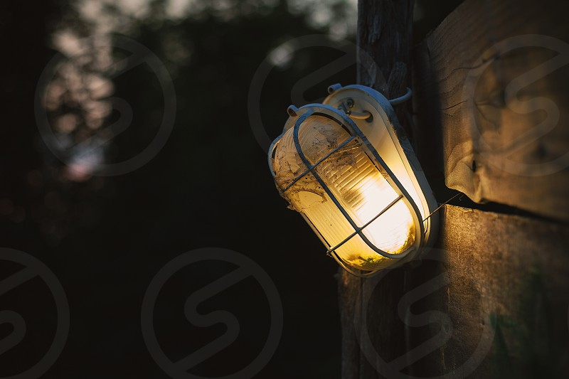 Details of a street broken lamp hanged on wooden board with blurry nature in background.  photo