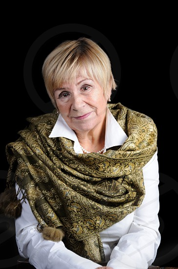 Portrait of an elderly woman in a white shirt with a shawl on her shoulders on a dark background close-up photo