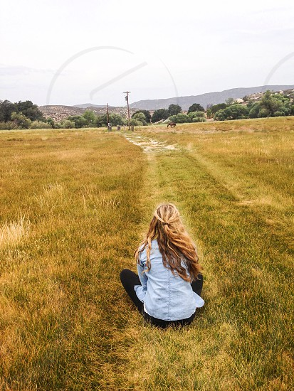 girl seated on grassy area gazing photo