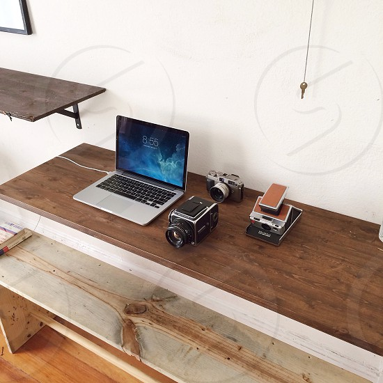 two cameras and macbook on brown table photo