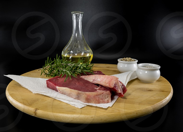 two entrecote steak on a wooden platter with olive oil rosemary salt and pepper ready for baking photo