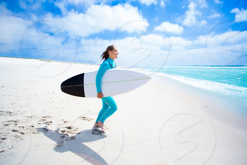 woman on the seashore holding surfing board photo