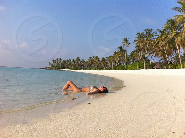 woman laying on beach with palm trees photo