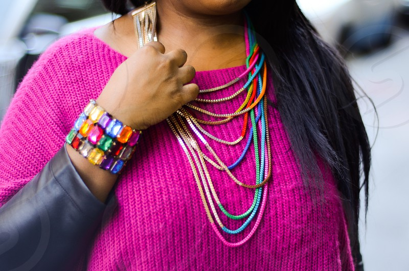woman in pink knit ribbed sweater and multicolored beaded necklaces photo