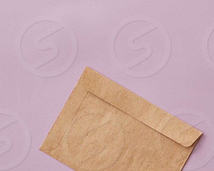 Wedding birthday or Valentines stationery craft paper envelope with copy space on a pink background. Flat lay photo