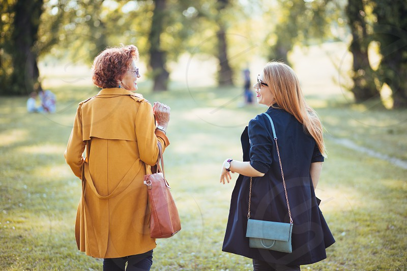 Mature mother and adult daughter enjoying a day in the park photo
