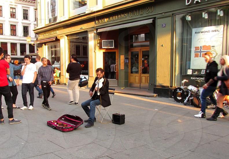 man playing a violin down the street photo