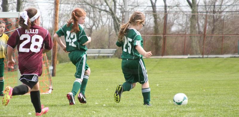 three children wearing green and maroon soccer jerseys on field photo