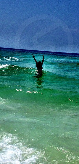 woman standing in green blue ocean water with both arms raised photo