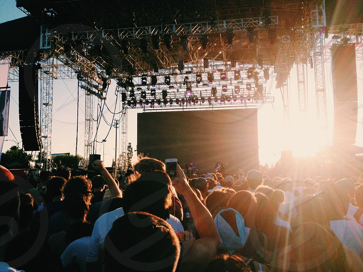 people in concert in front of stage during day photo
