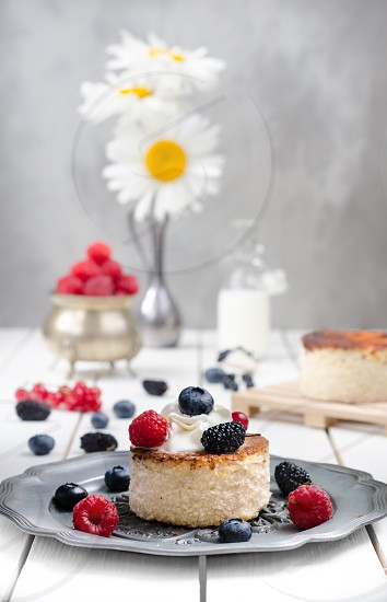 Ukrainian cheesecake with berries on old plate at white table photo