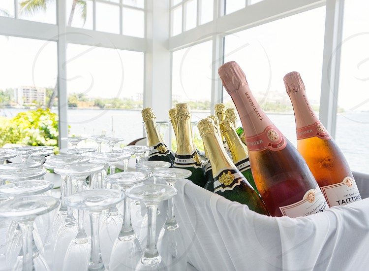 assorted types of wine piled in white cloth basket beside wine glasses in clear glass wall and door room photo