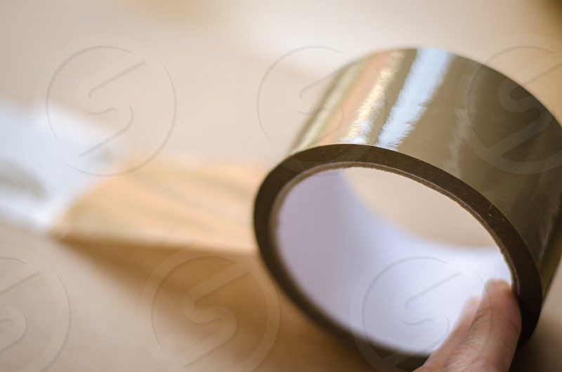 using tape to seal a box moving house packing up belongings photo