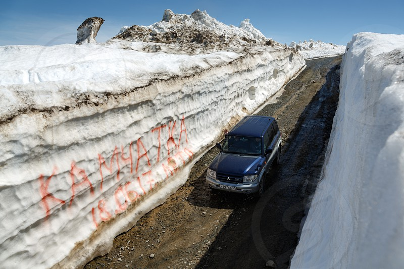 VILYUCHINSKY VOLCANO KAMCHATKA PENINSULA RUSSIA - JUNE 18 2017: Japanese off-road car Mitsubishi Pajero iO driving on mountain road in snow tunnel surrounded by high snowdrifts on Vilyuchinsky Pass photo