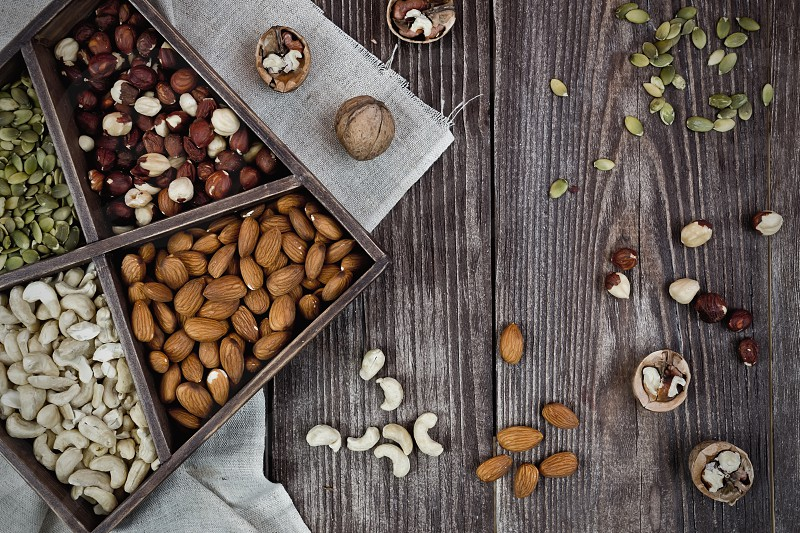Mix nuts on wooden box and table healthy vegan food. top view of paper tags photo