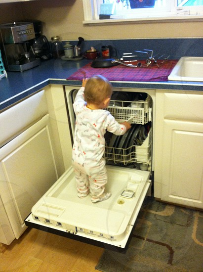 """Baby climbing on dishwasher door. """"The moment they discover how to climb; you realize if they can they will."""" photo"""