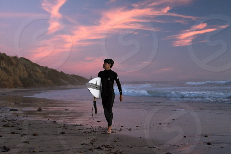 man in black wet suit holding surfboard walking near seashore during sunset photo