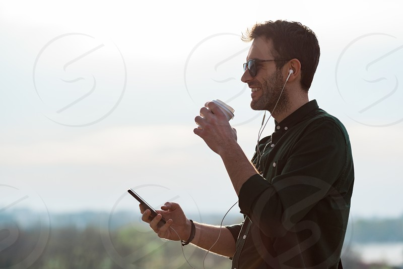 Young man drinking coffee listening to the music on the smartphone photo