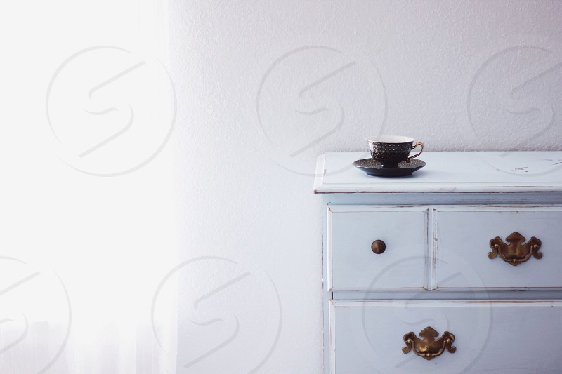 brown teacup on top of white drawer photo