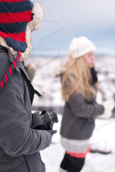 selective focus photography of person holding camera on snow photo