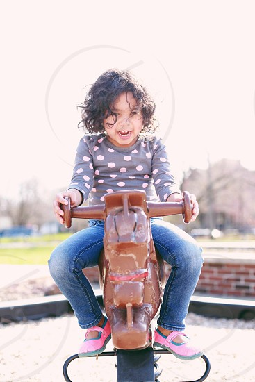 girl wearing blue jeans riding horse like toy photo