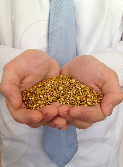 Hands holding gold nuggets photo