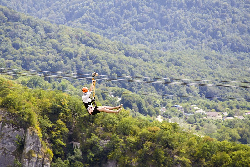 Man and woman hanging on a rope-way. Couple in helmets is riding on a cable car. Zipline is an exciting adventure activity. photo