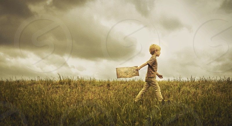 a young boy walks with a map across the top of a grassy hill.  photo