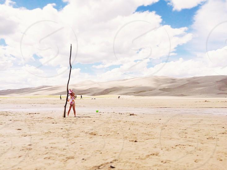 Girl child stick small strong desert dunes summer little play photo