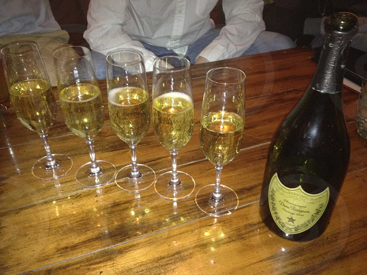 five champagne bottles with liquid photo