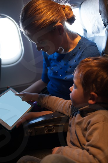 Attractive young mother traveling on a plane with her small son keeping him occupied playing on a tablet computer as he points to the screen photo