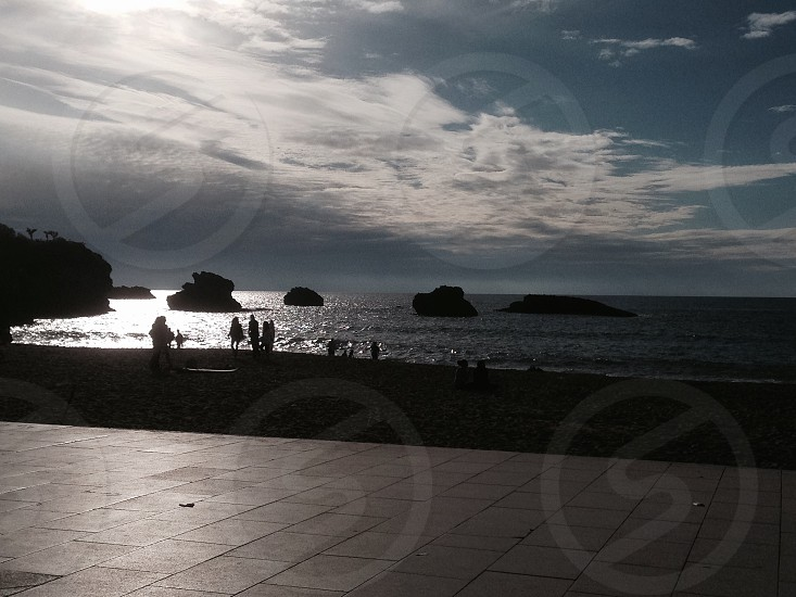 Silhouettes at dusk at Biarritz beach photo