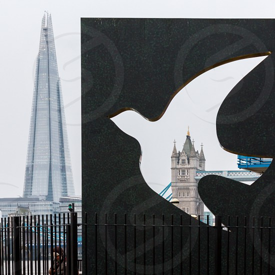 """the shard next to Tower Bridge framed through a sculpture from Wendy Taylor called """"the memorial to the civilians of east London""""  located in Wapping a district of East London. photo"""