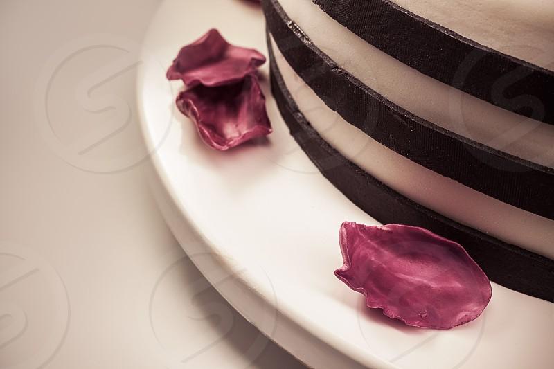 Details of a cake fallen purple petals made of sugar as decoration.  photo